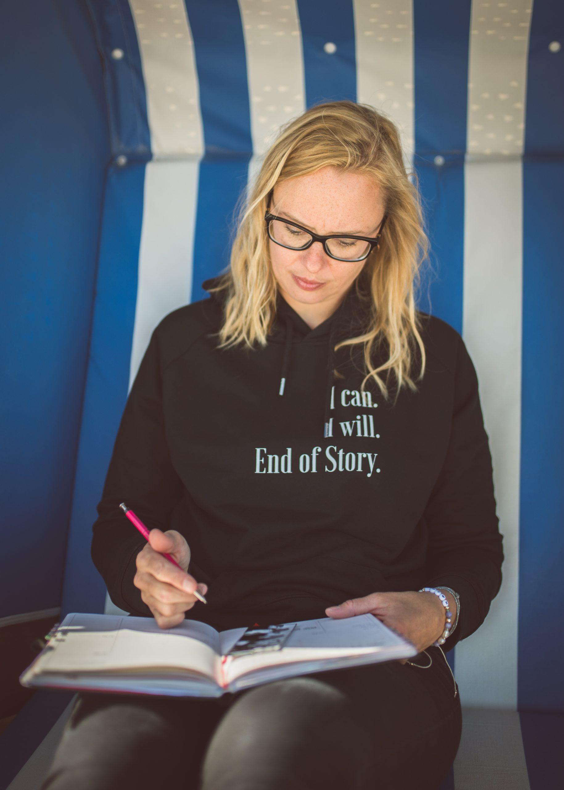 Gretel sitzt im Strandkorb und schreibt in ihren Planer