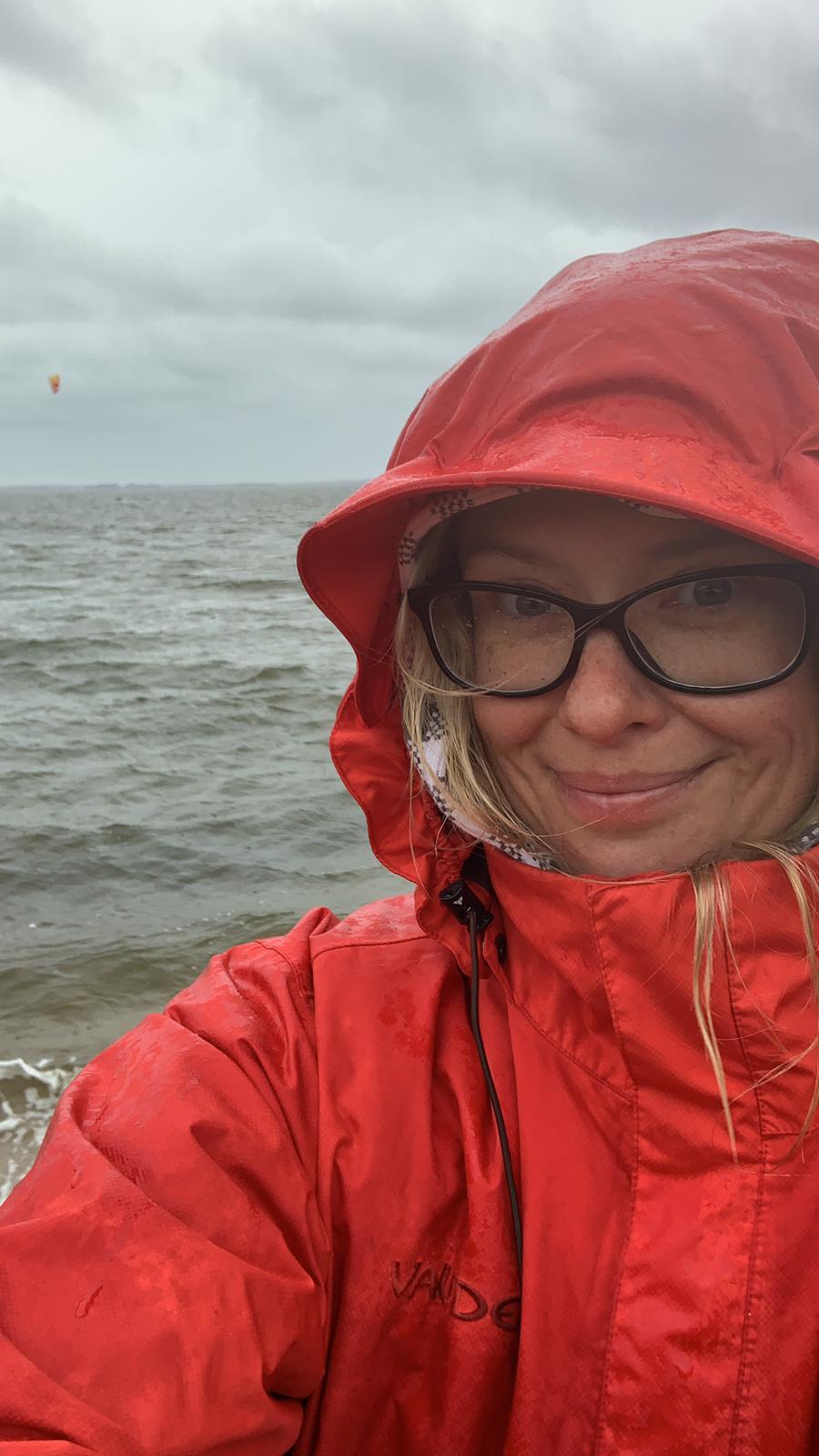 Gretel in Regenjacke bei Schietwetter vor grauem Himmel